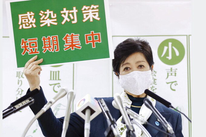 """Tokyo Gov. Yuriko Koike speaks during a news conference Wednesday, Nov. 25, 2020, in Tokyo. The board reads """"infection control measures, Short and intensive."""" (Kyodo News via AP)"""