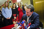 FILE - In this March 9, 2020 file photo with family members looking on, Montana Gov. Steve Bullock files paperwork to run for U.S. Senate against incumbent Republican Sen. Steve Daines in Helena, Mont. (Thom Bridge/Independent Record via AP,File)