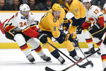 Calgary Flames defenseman Travis Hamonic (24) pokes the pucks away from Nashville Predators center Kyle Turris (8) during the second period of an NHL hockey game Thursday, Oct. 31, 2019, in Nashville, Tenn. (AP Photo/Mark Zaleski)