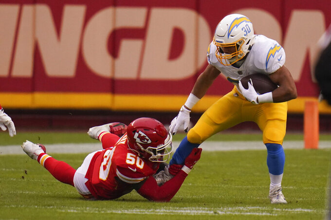 Los Angeles Chargers running back Austin Ekeler tries to break a tackle by Kansas City Chiefs linebacker Willie Gay (50) during the first half of an NFL football game, Sunday, Jan. 3, 2021, in Kansas City. (AP Photo/Jeff Roberson)