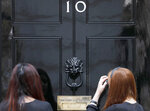 People wait at the entrance of 10 Downing Street in London, Wednesday, Aug. 28, 2019. Prime Minister Johnson has written to fellow lawmakers explaining his decision to ask Queen Elizabeth II to suspend Parliament as part of the government plans before the Brexit split from Europe. (AP Photo/Frank Augstein)
