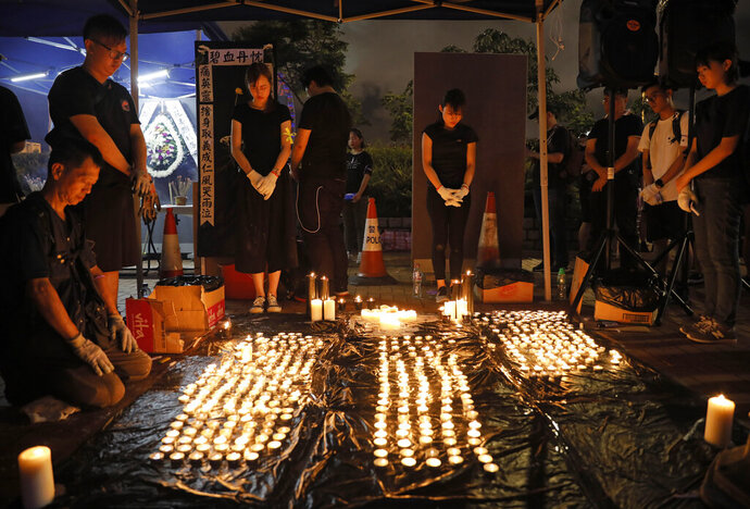 People pay during the one minute silent at a vigil to mourn the recent suicide of a woman due to the government's policy on the extradition bill in Hong Kong Saturday, July 6, 2019. A vigil is being held in Hong Kong for a woman who fell to her death this week, one of three apparent suicides linked to ongoing protests over fears that freedoms are being eroded in this semi-autonomous Chinese territory. (AP Photo/Vincent Yu)