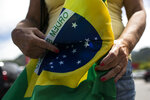 A former supporter of Brazil's President Jair Bolsonaro holds a Brazilian flag during a protest against the government's response in combating COVID-19 and demanding his impeachment, in Rio de Janeiro, Brazil, Sunday, Jan. 24, 2021. (AP Photo/Bruna Prado)