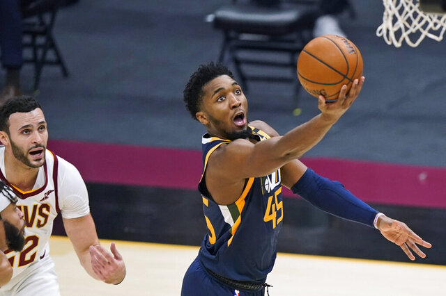 Utah Jazz's Donovan Mitchell (45) drives to the basket as Cleveland Cavaliers' Larry Nance Jr. watches during the first half of an NBA basketball game Tuesday, Jan. 12, 2021, in Cleveland. (AP Photo/Tony Dejak)
