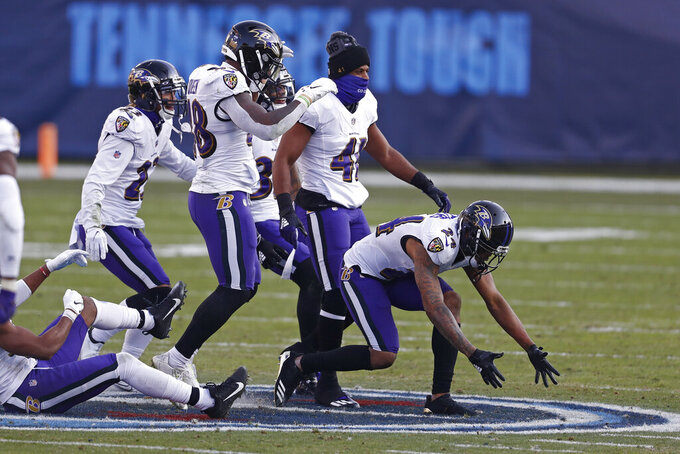 Baltimore Ravens cornerback Marcus Peters (24) and teammates dance on the Tennessee Titans' logo at the 50-yard line after Peters intercepted a pass late in the fourth quarter of an NFL wild-card playoff football game Sunday, Jan. 10, 2021, in Nashville, Tenn. The Ravens won 20-13. (AP Photo/Wade Payne)