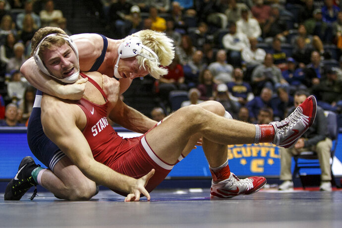 FILE - In this Jan. 2, 2019, file photo, Penn State's Bo Nickal, rear left, wrestles with Stanford's Nathan Traxler in the 197-pound championship bout of the Southern Scuffle wrestling tournament in Chattanooga, Tenn. Stanford announced Wednesday, July 8, 2020,  that it is dropping 11 sports amid financial difficulties caused by the coronavirus pandemic. The school will discontinue men's and women's fencing, field hockey, lightweight rowing, men's rowing, co-ed and women's sailing, squash, synchronized swimming, men's volleyball and wrestling after the 2020-21 academic year. Stanford also is eliminating 20 support staff positions.(C.B. Schmelter/Chattanooga Times Free Press via AP, File)