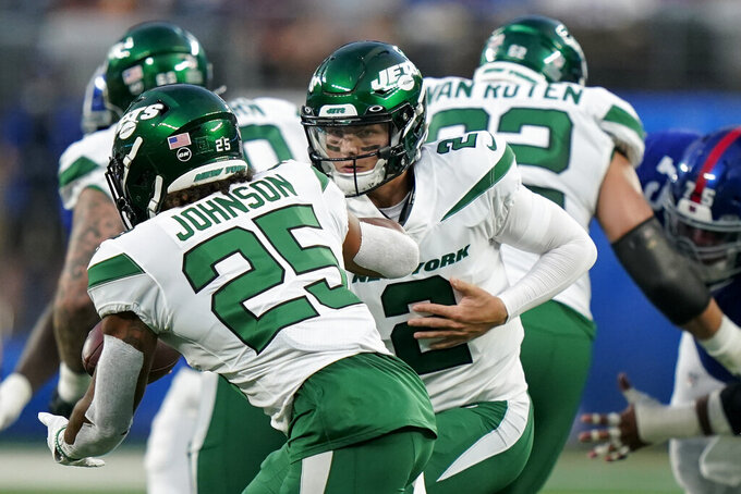 New York Jets quarterback Zach Wilson (2) fakes a handoff to running back Ty Johnson (25) in the first half of an NFL preseason football game against the New York Giants, Saturday, Aug. 14, 2021, in East Rutherford, N.J. (AP Photo/Corey Sipkin)