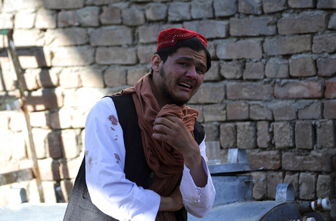 A Religious student cry inside a mosque after a bomb explosion in Shakar Dara district of Kabul, Afghanistan, Friday, May 14, 2021. A bomb ripped through a mosque in northern Kabul during Friday prayers killing 12 worshippers, Afghan police said. (AP Photo/Rahmat Gul)
