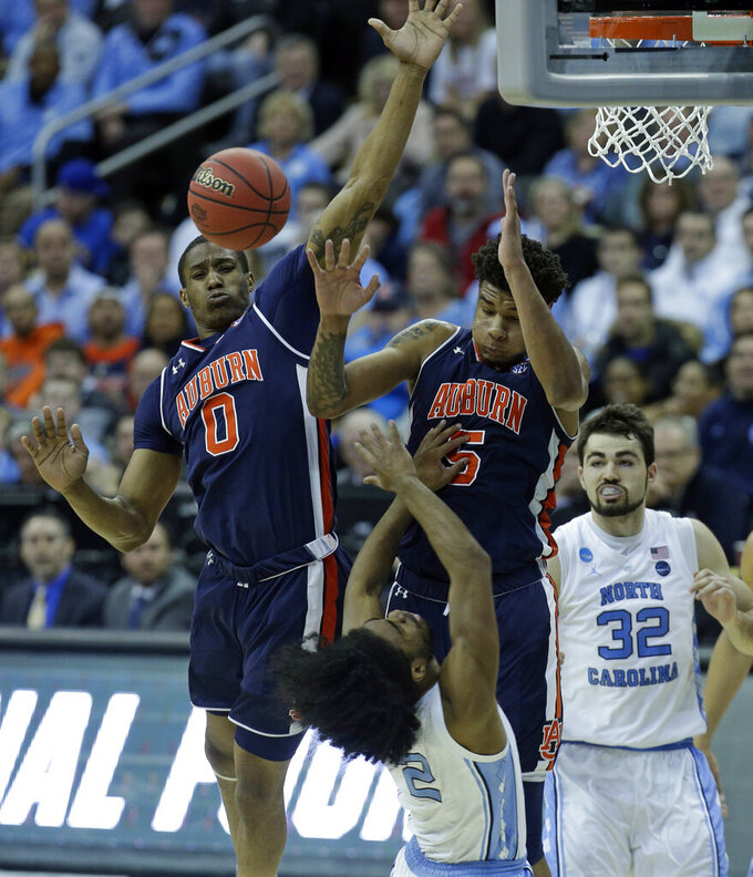 North Carolina's Coby White (2) loses control of the ball as Auburn's Horace Spencer (0) and Chuma Okeke (5) defend and teammate Luke Maye (32) watches during the first half of a men's NCAA tournament college basketball Midwest Regional semifinal game Friday, March 29, 2019, in Kansas City, Mo. (AP Photo/Charlie Riedel)