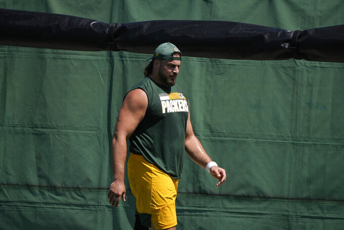 FILE - Green Bay Packers' David Bakhtiari runs a drill during an NFL football minicamp in Green Bay, Wis., in this June 8, 2021, file photo. Packers offensive tackle David Bakhtiari has used his big personality to make his presence felt in training camp even as he's unable to practice. He gave quarterback Aaron Rodgers a custom designed golf cart. He switched jerseys one day with new Packers offensive tackle Dennis Kelly, who bears more than a passing resemblance to him. How soon he'll be able to join those guys in an actual game remains uncertain.(AP Photo/Morry Gash, File)