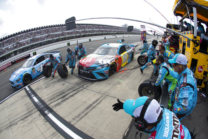 Kyle Busch (18) and Kevin Harvick (4) make pit stops during a NASCAR Cup Series auto race at Pocono Raceway, Sunday, June 2, 2019, in Long Pond, Pa. (AP Photo/Matt Slocum)