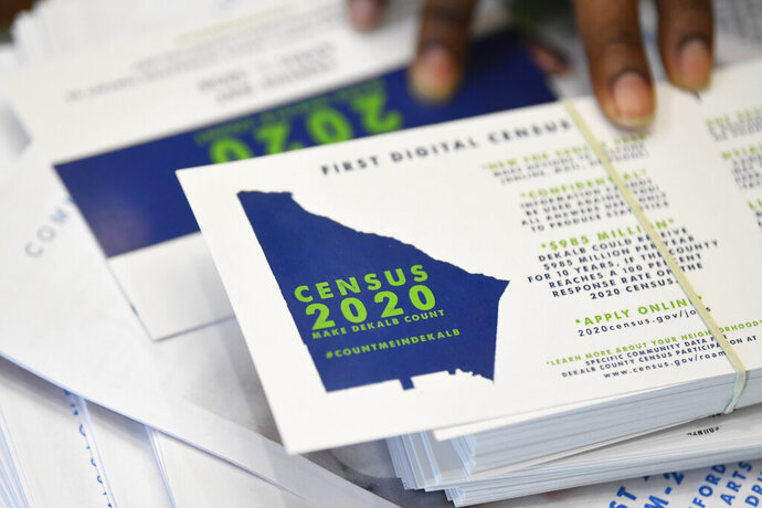 FILE - In this Aug. 13, 2019, file photo, a worker gets ready to pass out instructions in how fill out the 2020 census during a town hall meeting in Lithonia, Ga. Democrats are quick to blame President Donald Trump's single-minded efforts to overturn the Affordable Care Act for the increase in the nation's uninsured rate. But census numbers suggest other explanations as well, from the administration's immigration crackdown to the strong job market (AP Photo/John Amis, File)