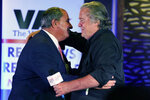 """Political strategist Steve Bannon, right, greets talks how host John Frederick, during an election rally in Richmond, Va., Wednesday, Oct. 13, 2021. Conservative radio host John Fredericks, a former Trump campaign chairman in Virginia, organized the """"Take Back Virginia Rally"""" in which former President Donald Trump called in. (AP Photo/Steve Helber)"""