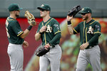 Oakland Athletics outfielders Seth Brown, left, Mark Canha, center, and Robbie Grossman celebrate after a baseball game against the Kansas City Royals, Thursday, Aug. 29, 2019, in Kansas City, Mo.  (AP Photo/Charlie Riedel)