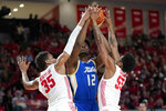 Tulsa's Emmanuel Ugboh (12) tries to shoot between Houston's Fabian White Jr. (35) and Brison Gresham (55) during the second half of an NCAA college basketball game Wednesday, Feb. 19, 2020, in Houston. (AP Photo/David J. Phillip)