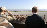 FILE - In this file photo taken on Tuesday, Dec. 12, 2017, Russian President Vladimir Putin, right, watches the troops marching as he and Syrian President Bashar Assad visit the Hemeimeem air base in Syria. Several private Russian military contractors were killed by a U.S. strike in Syria, Russian media reported Tuesday, Feb. 13, 2018 in a development that could further inflame Russia-U.S. tensions if officially confirmed. (Mikhail Klimentyev/Pool Photo via AP, File)