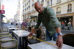 A man measures the distance between tables to respect social distance at a cafe terrace in Lille, northern France, Tuesday June 2, 2020. The French way of life resumes Tuesday with most virus-related restrictions easing as the country prepares for the summer holiday season amid the pandemic. Restaurants and cafes reopen Tuesday with a notable exception for the Paris region, the country's worst-affected by the virus, where many facilities will have to wait until June 22 to reopen. (AP Photo/Michel Spingler)
