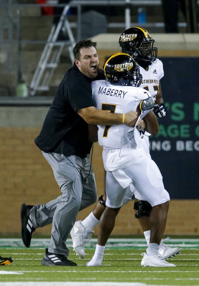 Southern Mississippi running back Darius Maberry (7) is congratulated by offensive line coach Ryan Stanchek after scoring a touchdown during the second half of an NCAA college football game against North Texas on Saturday, Oct. 3, 2020, in Denton, Texas. (AP Photo/Brandon Wade)