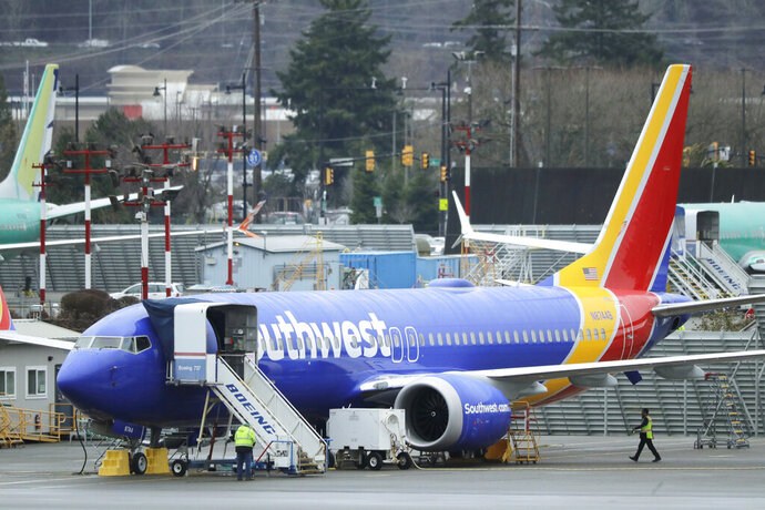 FILE - In this Dec. 11, 2019, file photo workers walk near a Southwest Airlines Boeing 737 Max airplane parked at Renton Municipal Airport in Renton, Wash. Southwest Airlines said Thursday, Jan. 16, 2020, that it has taken the grounded Boeing 737 Max out of its schedule until early June and is dropping more than 8% of its planned flights as a result. (AP Photo/Ted S. Warren, File)