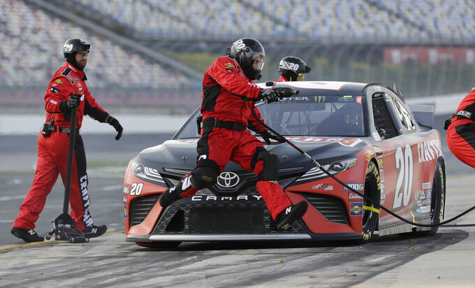 A crew member jumps past the front of driver Erik Jones's car during qualifying for Saturday's NASCAR All-Star Cup series auto race at Charlotte Motor Speedway in Concord, N.C., Friday, May 17, 2019. (AP Photo/Chuck Burton)