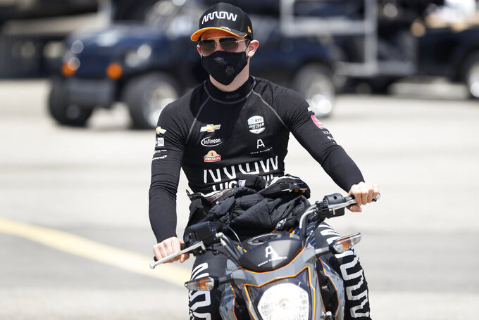 Pato O'Ward, of Mexico, makes his way to his car during practice for an IndyCar Series auto race Saturday, July 18, 2020, at Iowa Speedway in Newton, Iowa. (AP Photo/Charlie Neibergall)
