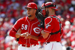 Cincinnati Reds starting pitcher Luis Castillo (58) meets with catcher Curt Casali (12) in the fourth inning of a baseball game against the Milwaukee Brewers, Thursday, Sept. 26, 2019, in Cincinnati. (AP Photo/John Minchillo)