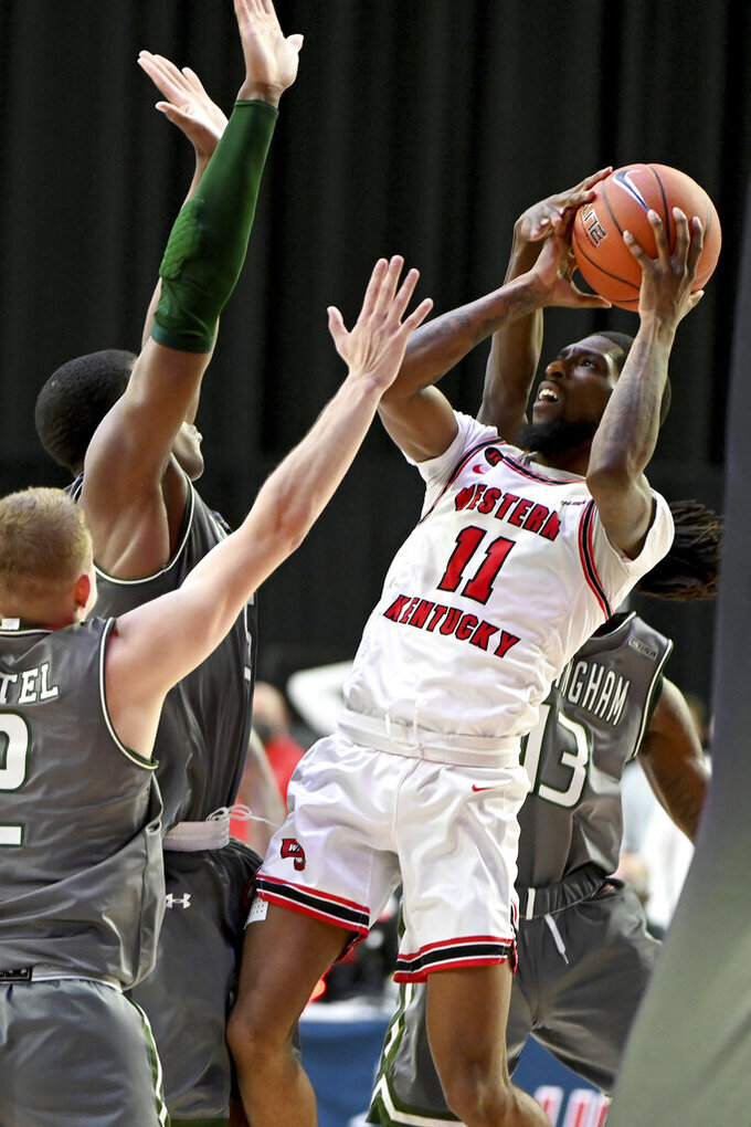 Western Kentucky guard Taveion Hollingsworth (11) drives the basket defended by UAB guard Quan Jackson (13), right, Trey Jemison (55) and guard Michael Ertel (2), left, in the first half of an NCAA college basketball game in the Conference USA men's tournament, in Frisco, Texas, Friday, March 12, 2021. (AP Photo/Matt Strasen)