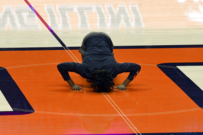 Illinois' Ayo Dosunmu kisses court before the team's last home game of the NCAA college basketball season, against Nebraska on Thursday, Feb. 25, 2021, in Champaign, Ill. Dosunmu missed the game with a broken nose. (AP Photo/Holly Hart)