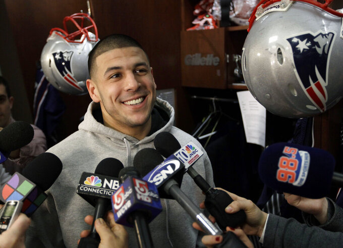 FILE - In this Jan. 26, 2012, file photo, New England Patriots tight end Aaron Hernandez speaks to reporters at his locker at the NFL football stadium in Foxborough, Mass. A federal judge says the 6-year-old daughter of deceased NFL player Aaron Hernandez missed a 2014 deadline to opt out of the $1 billion concussion settlement and can't separately sue the league over his CTE diagnosis. Yet Hernandez's death in 2017 came too late for his family to seek compensation for CTE-related suicides under the class action settlement. 