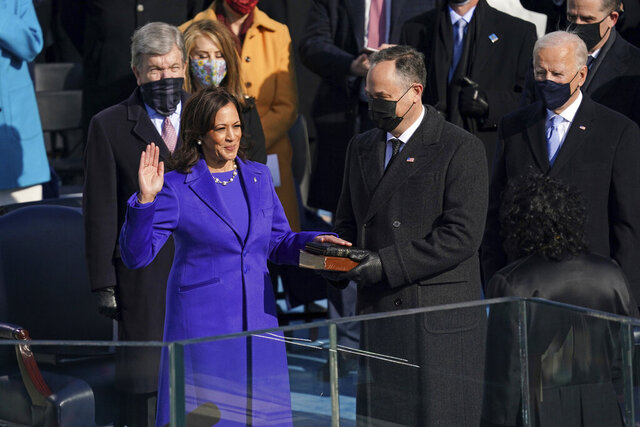 FILE - Kamala Harris is sworn in as vice president by Supreme Court Justice Sonia Sotomayor as her husband Doug Emhoff holds the Bible during the 59th Presidential Inauguration at the U.S. Capitol in Washington, Wednesday, Jan. 20, 2021.   On Friday, Jan. 22, The Associated Press reported on stories circulating online incorrectly claiming Kamala Harris put her hand on a purse instead of a Bible during her swearing in.  (Erin Schaff/The New York Times via AP, Pool, File)