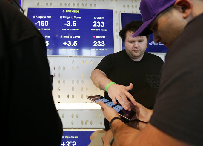 FILE - In this March 19, 2019, file photo, Zack Shelton, left, of Swish Analytics, explains how to place a bet at the Skyloft Predictive Gaming Lounge inside the Golden 1 Center, home of the NBA's Sacramento Kings, in Sacramento, Calif. Professional sports leagues have found a way to cash in by selling their official data to gambling companies, making the case that the leagues are creating new products for gamblers to bet on. (AP Photo/Rich Pedroncelli, File)