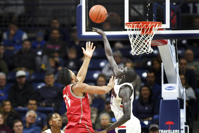 Connecticut's Akok Akok (23) gets one of his four blocks in the second half against Sacred Heart's E.J. Anosike (24) during an NCAA college basketball game Friday, Nov. 8, 2019, in Storrs, Conn. (AP Photo/Stephen Dunn)