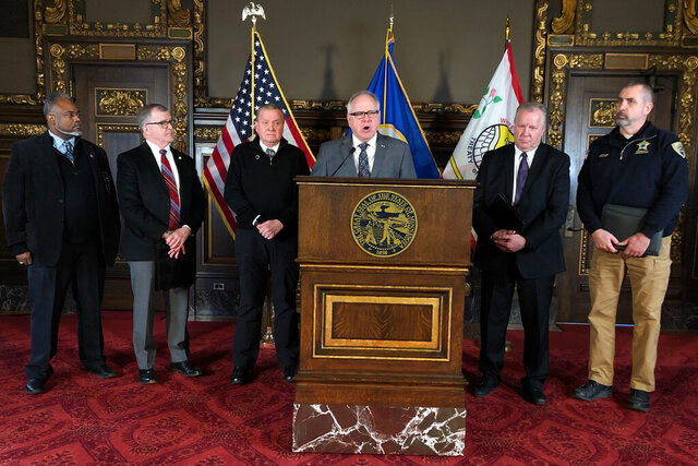 Minnesota Gov. Tim Walz, center, is flanked by state and county emergency managers at a news conference at the state Capitol in St. Paul, on Tuesday, Feb. 18, 2020, as he asks lawmakers to approve $30 million to replenish a state disaster aid fund that was drained by a string of disasters last year. (AP Photo/Steve Karnowski)