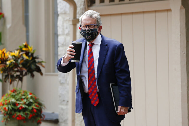 Ohio Gov. Mike DeWine acknowledges members of the media while entering his residence after testing positive for COVID-19 earlier in the day Thursday, Aug. 6, 2020, in Bexley, Ohio.  DeWine tested positive using a rapid test Thursday, before testing negative later in the day using a more sensitive laboratory-developed test.  No test for coronavirus infection is perfect, and test results can be affected by a variety of factors, including the type of test used, the quality of the sample and when it was taken during the course of any infection. (AP Photo/Jay LaPrete)