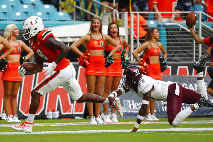 Bethune-Cookman safety Donald Johnson IV (37) attempts to take down Miami wide receiver Dee Wiggins (8) during the first half of an NCAA college football game Saturday, Sept. 14, 2019, in Miami Gardens, Fla. (AP Photo/Wilfredo Lee)