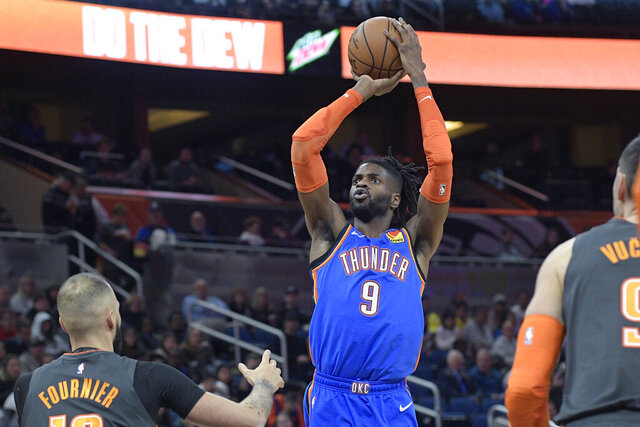 Oklahoma City Thunder center Nerlens Noel (9) goes up for a shot between Orlando Magic guard Evan Fournier, left, and center Nikola Vucevic (9), right, during the first half of an NBA basketball game Wednesday, Jan. 22, 2020, in Orlando, Fla. (AP Photo/Phelan M. Ebenhack)