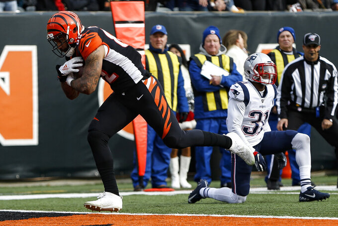 Cincinnati Bengals tight end Cethan Carter, left, runs in a touchdown after breaking a tackle from New England Patriots cornerback Jonathan Jones (31) in the first half of an NFL football game, Sunday, Dec. 15, 2019, in Cincinnati. (AP Photo/Frank Victores)