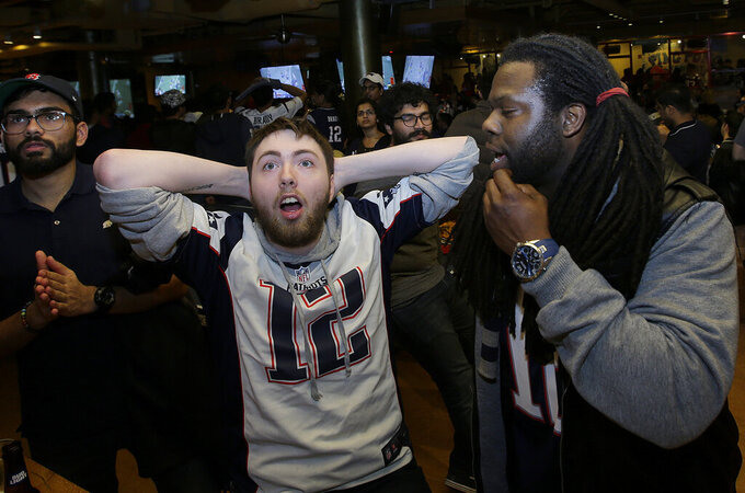Ivan Cady, center, of Milford N.H., and Ernest Carr, right, of Las Vegas, react after an interception thrown by New England Patriots' Tom Brady while watching the first half of the NFL Super Bowl 53 football game in Atlanta between the Patriots and the Los Angeles Rams at a bar in Boston, Sunday, Feb. 3, 2019. (AP Photo/Steven Senne)
