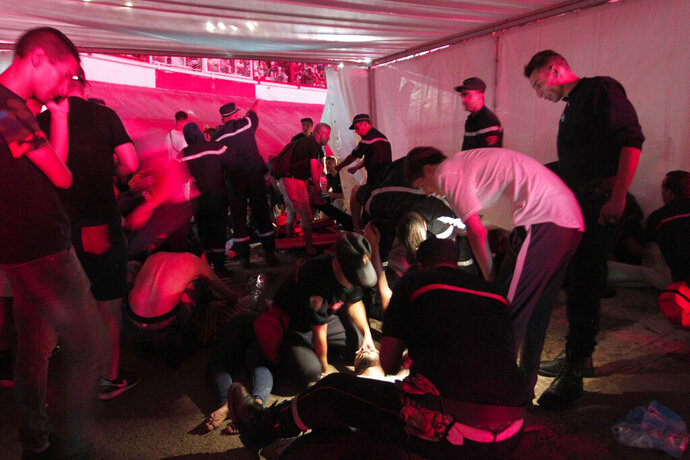 People are being tended by rescue workers during Algerian rap artist Abderraouf Derradji's concert, known as Soolking, at a stadium in Algiers, Thursday, Aug. 22, 2019. The concert caused some deaths and injuries in a stampede as fans thronged an entrance at the rap concert in the Algerian capital. (AP Photo/Fateh Guidoum)