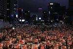 In this Aug. 15, 2019 photo, protesters hold candles and signs during a rally denouncing Japanese Prime Minister Shinzo Abe and also demanding the South Korean government to abolish the General Security of Military Information Agreement, or GSOMIA, an intelligence-sharing agreement between South Korea and Japan, in downtown Seoul, South Korea. South Korea and Japan have locked themselves in a highly-public dispute over history and trade that in a span of weeks saw their relations sink to a low unseen in decades.  The letters read