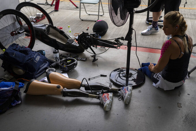 Oksana Masters, from USA, sits next to her bike after wining at women's H4-5 Time Trial at the Fuji International Speedway at the Tokyo 2020 Paralympic Games, Tuesday, Aug. 31, 2021, in Tokyo, Japan. (AP Photo/Emilio Morenatti)