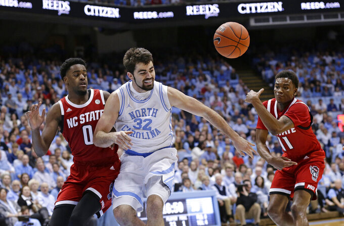 North Carolina's Luke Maye (32) loses the ball while driving to the basket against North Carolina State's DJ Funderburk (0) and Markell Johnson (11) during the first half of an NCAA college basketball game in Chapel Hill, N.C., Tuesday, Feb. 5, 2019. (AP Photo/Gerry Broome)