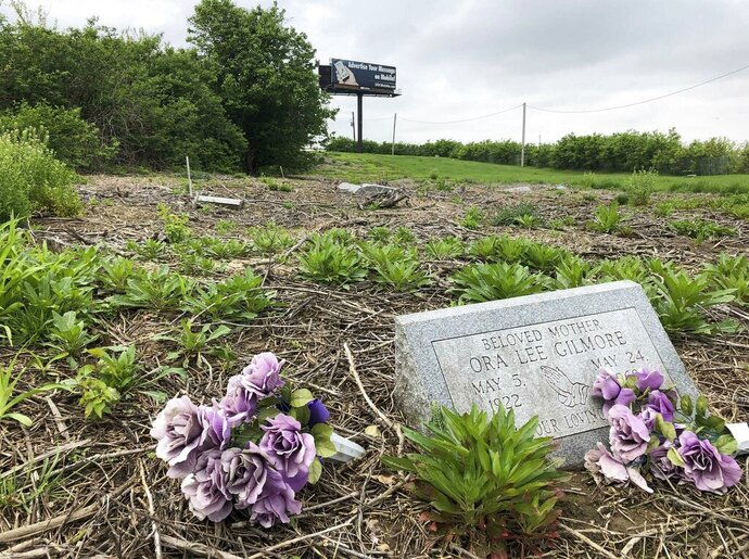 A billboard towers over a grave marker in the African-American Washington Park Cemetery in Berkeley, Mo., Tuesday, April 23, 2019. A lawsuit filed in St. Louis County asks a judge to issue an order requiring removal of billboards that tower above the suburban St. Louis town's cemetery. Wanda Brandon's lawsuit claims the billboards are disrespectful to the people buried there, including her mother and grandmother. (AP Photo/Jim Salter)