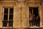 A woman and her children applaud after they set up candles on their balcony in Versailles, Wednesday, March 25, 2020. France's bishops called for Catholics and non-Catholics alike to take part in Wednesday's candle-lighting, in a shared