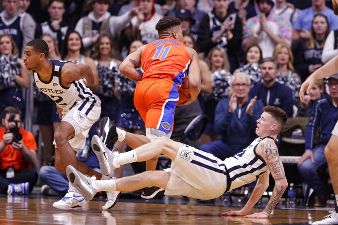 Butler forward Sean McDermott (22) goes to the floor after fouling Florida forward Keyontae Johnson (11) in the first half of an NCAA college basketball game in Indianapolis, Saturday, Dec. 7, 2019. (AP Photo/Michael Conroy)