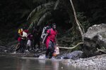 Migrants cross the Acandi River on their way north, in Acandi, Colombia, Wednesday, Sept. 15, 2021. The migrants, following a well-beaten, multi-nation journey towards the U.S., will continue their journey through the jungle known as the Darien Gap. (AP Photo/Fernando Vergara)