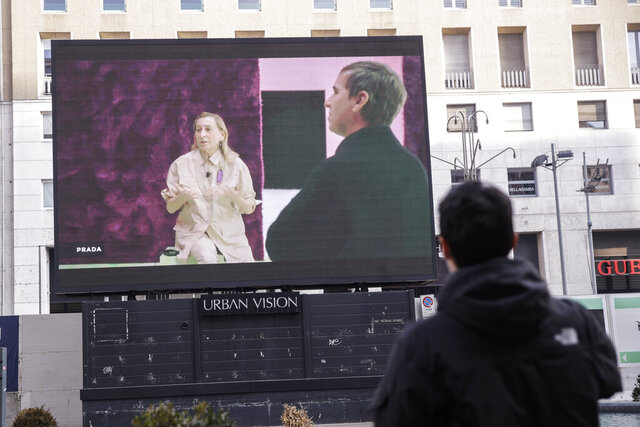 A giant screen streams a Prada fashion live during an interview with Miuccia Prada and Raf Simons, during the Milan's fashion week in Milan, Italy, Sunday, Jan. 17, 2021. (AP Photo/Luca Bruno)