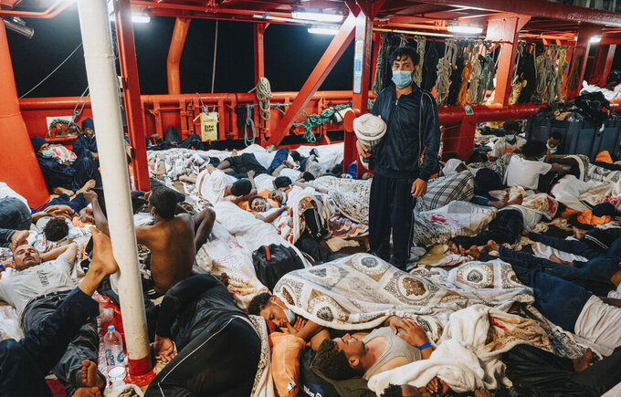Migrants sleep on the deck of the Ocean Viking rescue in the Mediterranean Sea on Tuesday, July 5, 2021. A charity rescue ship with 572 migrants aboard on Thursday, July 8, 2021 pleaded for permission to dock at some Mediterranean port as food aboard was reporting running short. Luisa Albera,  search and rescue coordinator of SOS MEDITERRANEE, launched an urgent appeal from aboard the Ocean Viking. She said five requests to maritime authorities to assign a port of safety have gone unmet and tensions aboard the ship are worsening after several days in very crowded conditions. (Flavio Gasperini/SOS Mediterranee via AP)