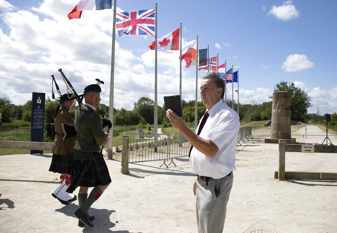 British expatriate Steven Oldrid, right, films a group crossing over the site of the original WWII Pegasus Bridge during D-Day ceremonies in Benouville, Normandy, France on Saturday, June 6, 2020. Due to coronavirus measures many relatives and veterans will not make this years 76th anniversary of D-Day. Oldrid will be bringing it to them virtually as he places wreaths and crosses for families and posts the moments on his facebook page. (AP Photo/Virginia Mayo)