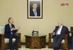 In this photo released by the Syrian official news agency SANA, Syria's Foreign Minister Walid al-Moallem, right, meets with the United Nations' new special envoy for Syria, Geir Pedersen, in Damascus, Syria, Tuesday, Jan. 15, 2019. Turkey's President Recep Tayyip Erdogan said Tuesday that his troops will establish a 20-mile-wide